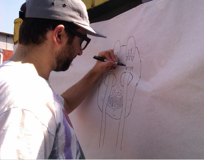 Daniel Harris drawing on sketch paper that has been wrapped around a dumpster